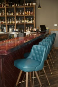 The bar inside 55 South, complimented by a row of teal blue bar chairs.