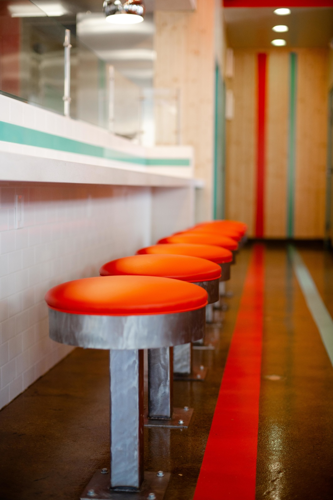 A detailed look at the retro metal and red vinyl lunch counter stools.