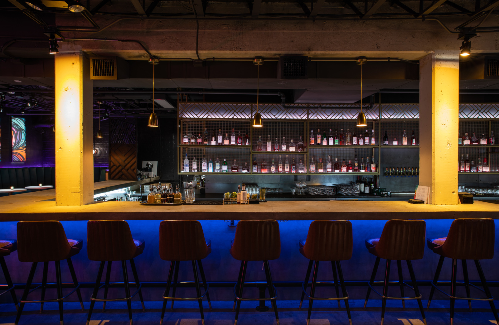An image of the bar at Rambler with brown leather stools and neon lights