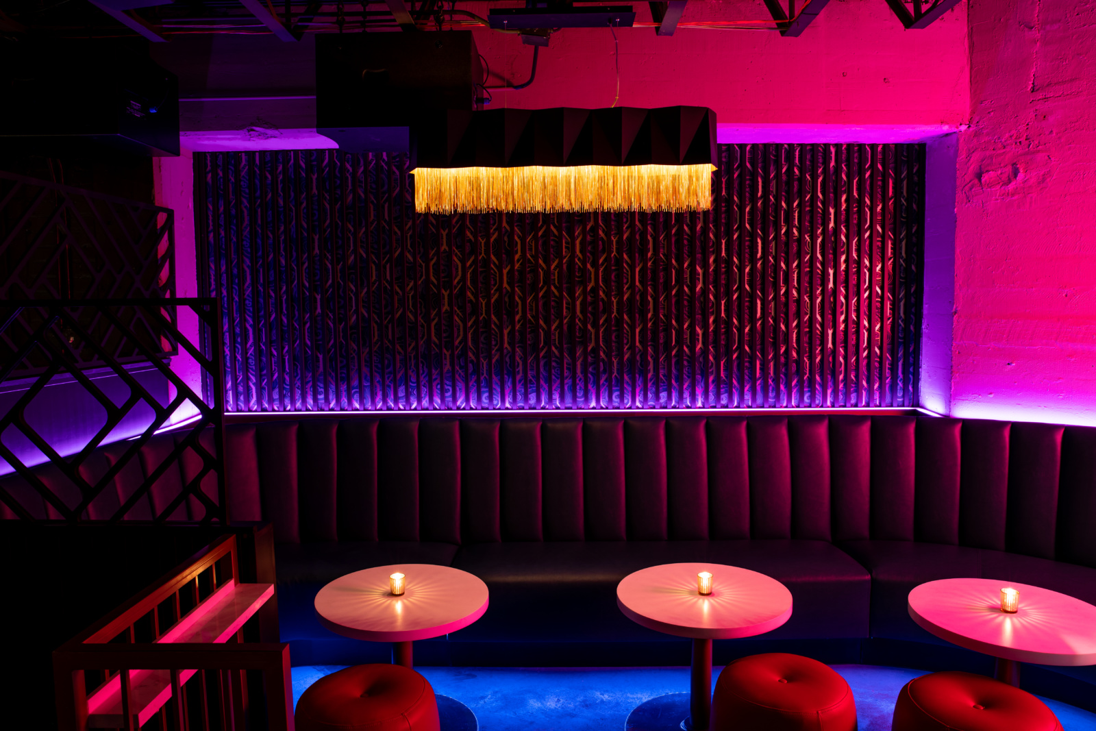 Neon lights, custom made booths, and extravagant light fixture at Rambler