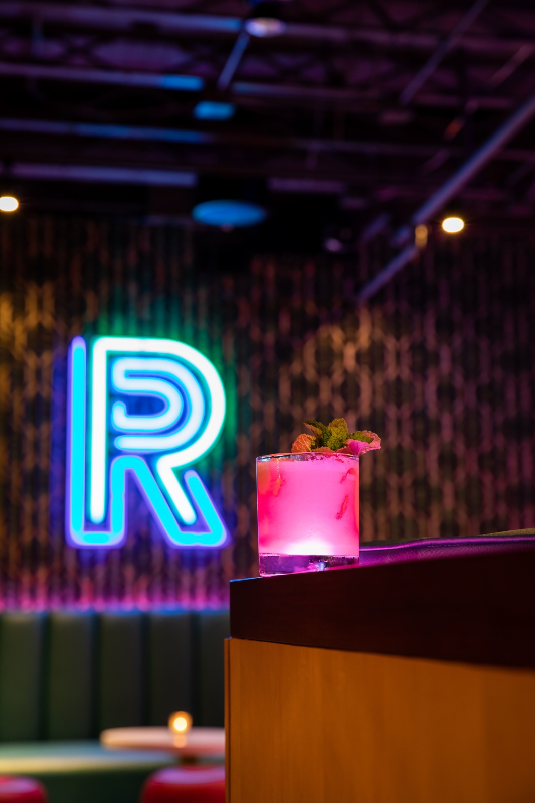 "A neon lit drink with the neon ""R"" behind it at Rambler"