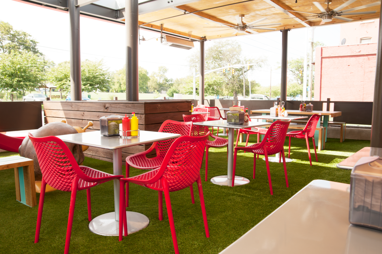 The outside patio with red chairs and green turf at Hugh Baby's