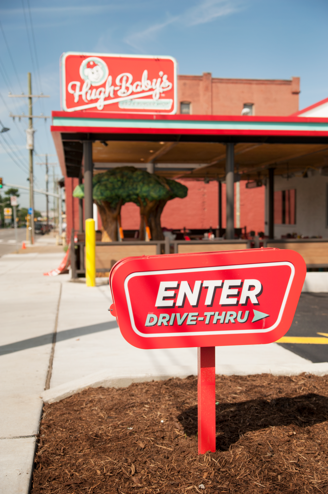 The drive through enter sign with Hugh Baby's restaurant in the back.