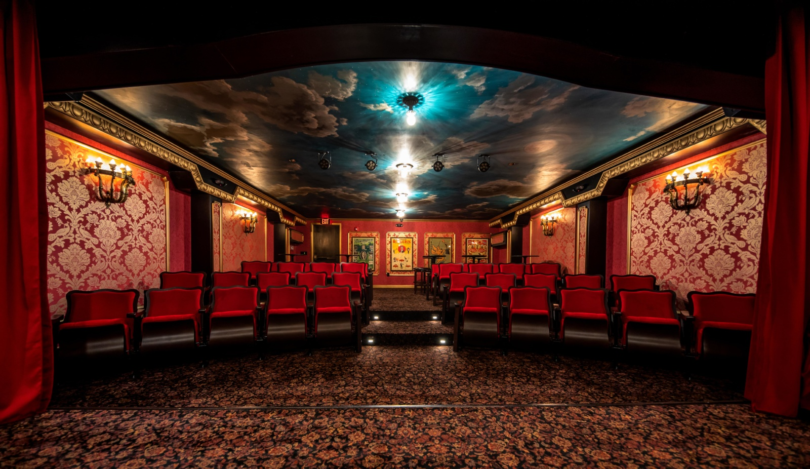 A look into the theater at House of Cards with a sky mural on the ceiling, warm and rich velvet curtains and theater seats, and rich details throughout.